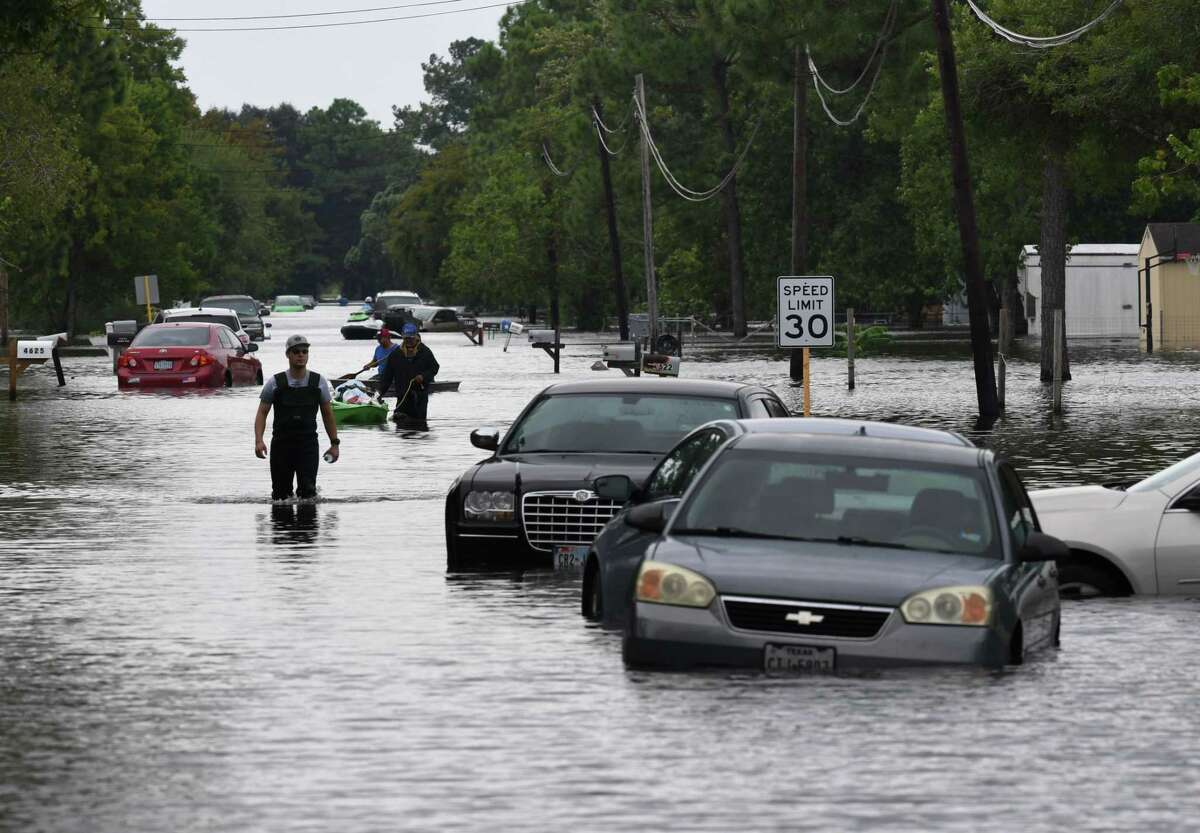 Residents wade through flooded streets in Crosby, Texas, on Wednesday.