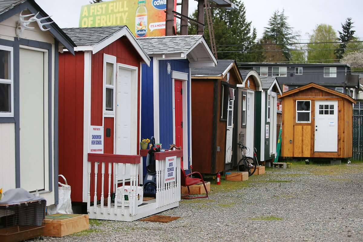 """Colorful tiny houses are lined up at the new Licton Springs tiny house village, which opened April 5. The Low Income Housing Institute's sixth village has 30 tiny houses and both men's and women's overflow dorm tents. Photographed April 23, 2017. Licton Springs is the only village that does not allow minors and is """"low-barrier,"""" residents are not required to be clean and sober on site as long as good behavior is maintained. (Genna Martin, seattlepi.com)"""