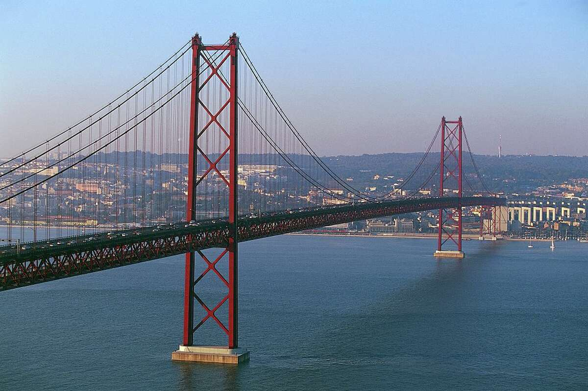 Doppelganger: The 25 de Abril Bridge in Lisbon, Portugal The resemblance isn't accidental. The 25 de Abril Bridge, spanning the Tagus River between Lisbon and Almada, was constructed in 1966 by the same American consortium that made the Bay Bridge, with U.S. steel. At first glance the 25 de Abril looks just like the Golden Gate Bridge, thanks to that unmistakable International Orange paint job. Take a closer look and you'll see the tower design looks just like the Bay Bridge's. Also like the latter Bay Area bridge, it has two decks, though the bottom one is for trains. The top deck has six car lanes, as the Golden Gate does. Another subtle resemblance between the Portuguese and Golden Gate bridges? For Lisbon residents it's a familiar crossing for road trips to Portugal's wine regions. The Portuguese landmark was initially named the Salazar Bridge until it was changed to honor the date of the bloodless Carnation Revolution in 1974.