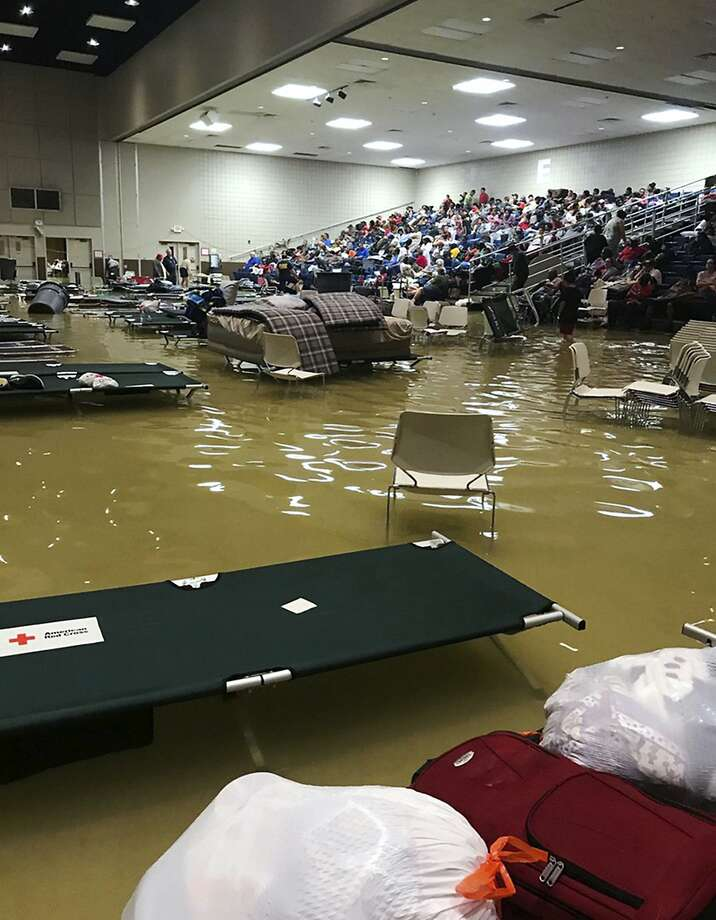 """Evacuees sit in the bleachers at a civic center in Port Arthur, Texas, after floodwaters inundated the facility overnight. The mayor said on Facebook, """"city is underwater right now."""" Photo: Beulah Johnson, Associated Press"""