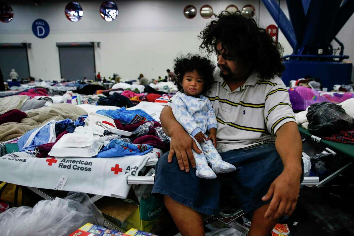 Edgar Molina holds his one-year-old daughter, Miracle Marie Molina, on a cot at the George R. Brown Convention Center where nearly 10,000 people are taking shelter after Tropical Storm Harvey Wednesday, Aug. 30, 2017 in Houston. Molina and his daughter have been at the shelter since Sunday.