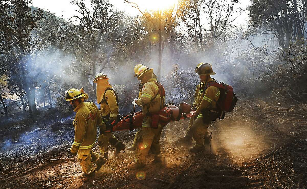 In this Tuesday, Aug. 8, 2017 photo, firefighters carry an injured California Department of Corrections inmate firefighter along the fire line to an awaiting ambulance in Kelseyville, Calif. (Kent Porter/The Press Democrat via AP)