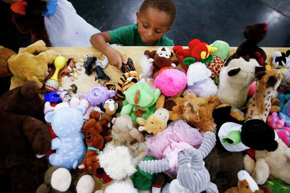Jacob Evans, 4, picks out a toy from a donations table at the George R. Brown Convention Center where nearly 10,000 people are taking shelter after Tropical Storm Harvey Wednesday, Aug. 30, 2017 in Houston.