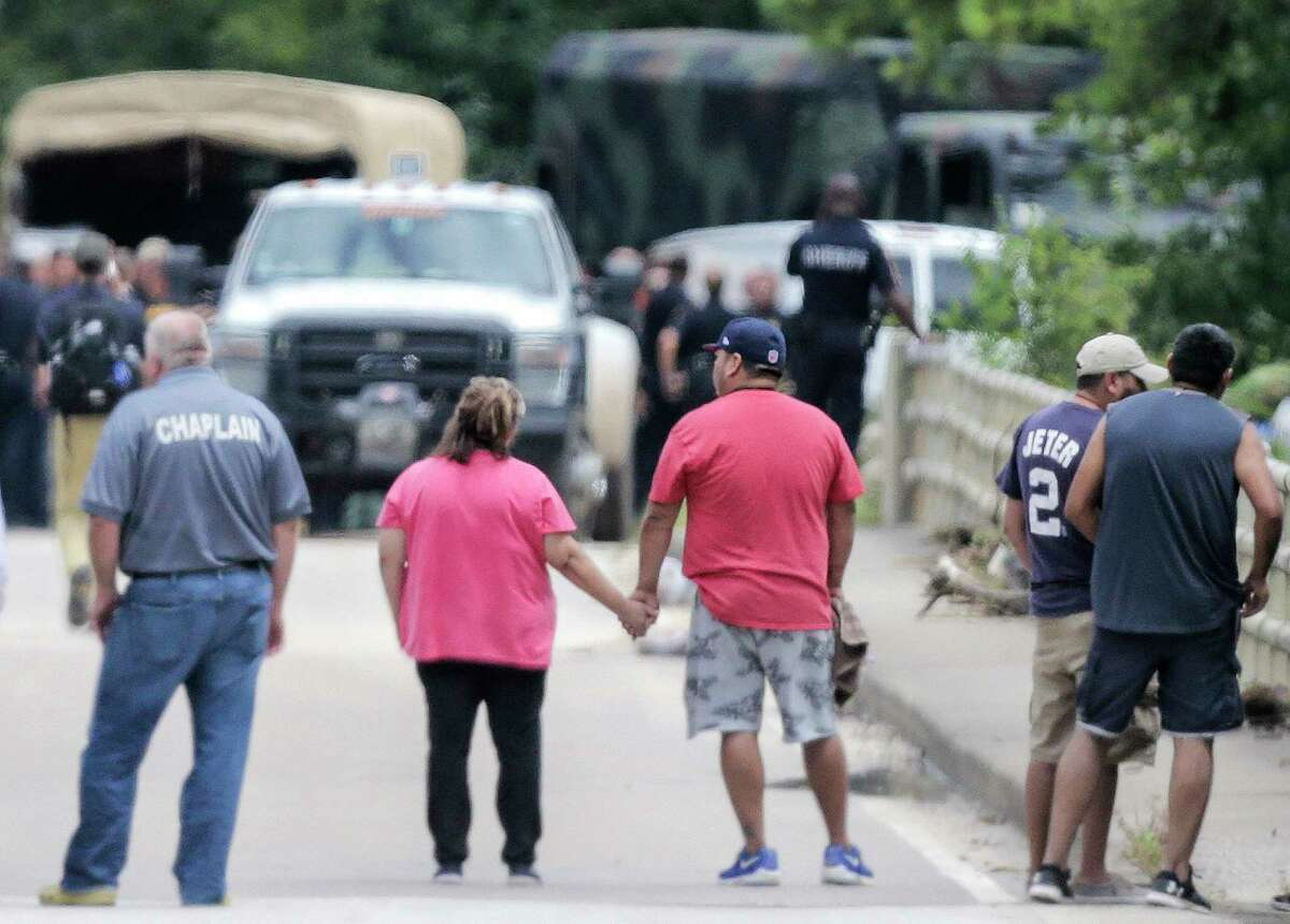Family members hold hands as recovery efforts underway after Tropical Storm Harvey left the Houston area on Wednesday, Aug. 30, 2017, in Houston. The bodies of six members of the Saldivar family were discovered in the van they were last seen driving during the storm.