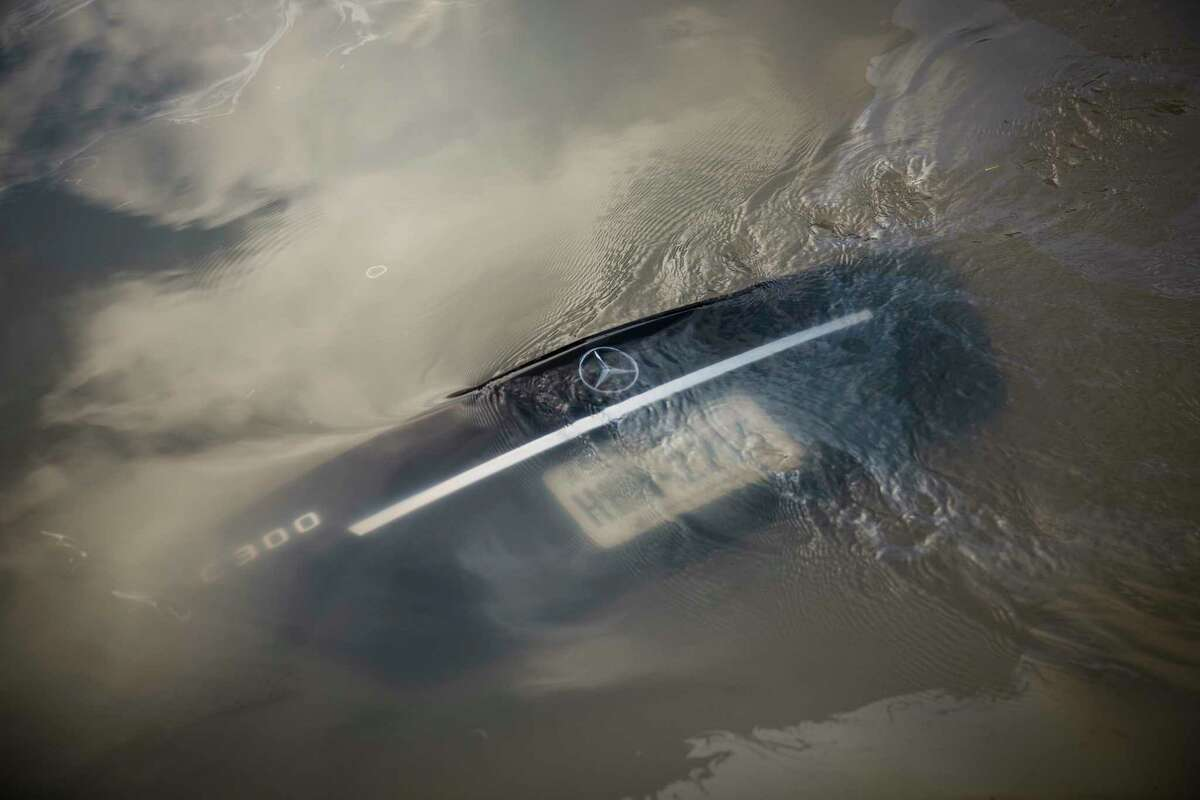 Water from the Addicks Reservoir flows over the trunk of a submerged Mercedes in a west Houston neighborhood.