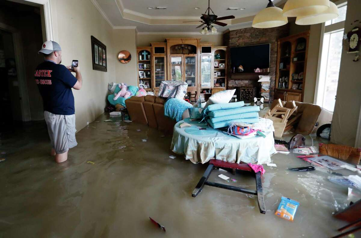 Tim Stamps takes a photo his dad's house surrounded by 6-7 feet of water in the Kingwood Greens Subdivision from the San Jacinto River due to Tropical Storm Harvey, Wednesday, Aug. 30, 2017, in Kingwood. Stamps was there to help his dad, Mike, retrieve his two cats, who had to be left behind, as he was evacuated on a jet ski Tuesday.