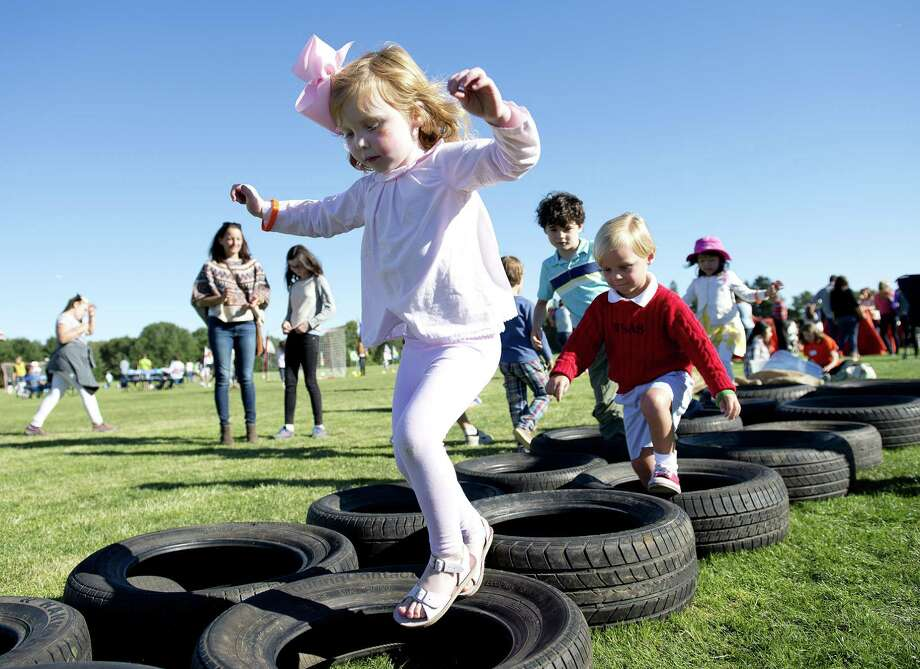 Catherine Eagan, 4, jumps through tires as she plays at the 17th annual Go Wild! event held by the Greenwich Land Trust at Greenwich Polo Club in 2016. This year's Go Wild! event is set for Sept. 24. Photo: Lindsay Perry / For Hearst Connecticut Media / Greenwich Time Freelance