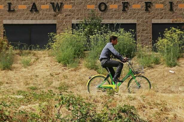 A man rides a LimeBike down the Burke Gilman Trail near Gas Works Park, Wednesday, Aug. 30, 2017.