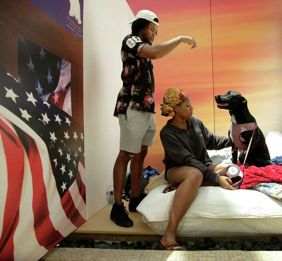 Preston Opara and his sister Chelsea entertain their dog, Olive, while sheltering in Gallery Furniture Wednesday, Aug. 30, 2017, in Richmond, Texas. Photo: Charlie Riedel, Associated Press / Copyright 2017 The Associated Press. All rights reserved.
