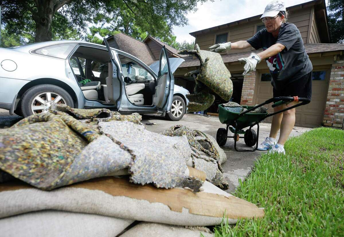 Susan Henney tosses wet carpet as she helps her neighbors clean up from flooding on Wednesday in Houston. The city and surrounding area was flooded in the aftermath of Hurricane Harvey. The IRS said it is making it easier for storm victims to take money out of their employer-sponsored retirement plans.