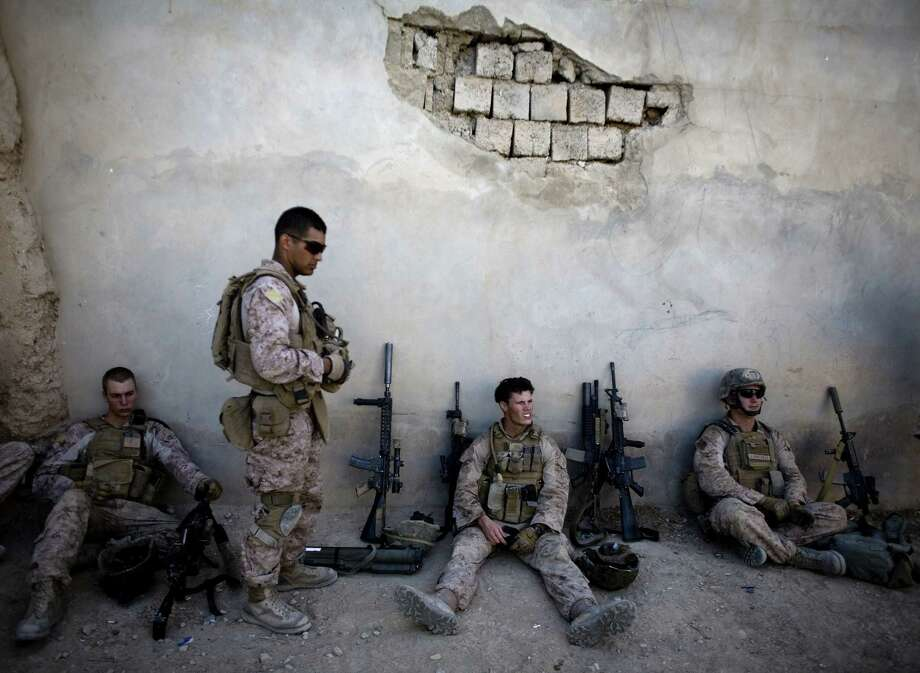 Marines of with India Company, 3rd Battalion 5th Marines, First Marine Division, take a break during a patrol in Sangin, south of Kabul, Afghanistan in 2011. Reversing his past calls for a speedy exit, President Donald Trump recommitted the United States to the 15-year-old war in Afghanistan, declaring that U.S. troops must fight to win. Critics say a broader strategy is needed. Photo: Dusan Vranic /Associated Press / AP2010
