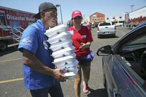 H.E.B. Disaster Relief team members Albert Rodriguez and Kristina Leal hand out free meals to an endless line of cars as recovery proceeds in Rockport on Wednesday. An impromptu fund drive in Del Rio will pay for bottled water that the grocery chain is distributing there.