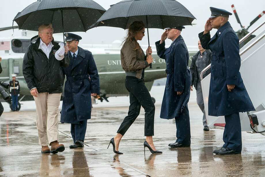 """President Donald Trump and first lady Melania Trump board Air Force One for a trip to Texas, at Joint Base Andrews in Maryland, Aug. 29, 2017. When is a shoe not just a shoe? When it is a pair of very high, needle-thin heels worn by the first lady on her way to the site of a natural disaster. Though by the time the plane had landed Melania Trump had changed to white sneakers and crisp white shirt, with a ponytail pulled through a black baseball cap emblazoned with the word �FLOTUS."""" During her time in the air the original heels went from being mere footwear to objects of vilification thanks to social media�s specific kind of alchemy. (Doug Mills/The New York Times) Photo: DOUG MILLS, NYT"""