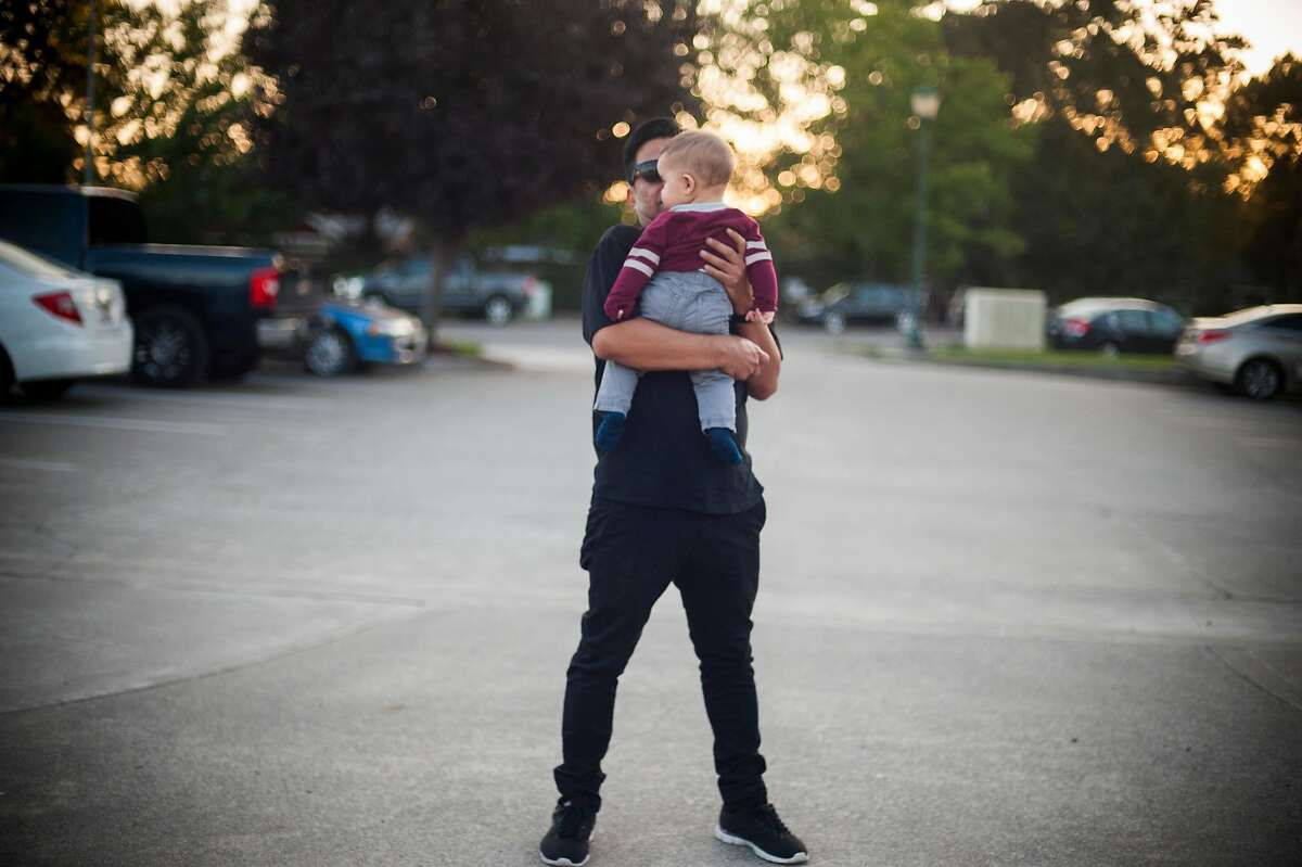 Gerardo Lopez consoles himself holding a 7-month-old outside memorial service held for Veronica Cabrera Ramirez on August 29, 2017 in Windsor, CA. Ramirez was allegedly killed by her boyfriend, Nery Israel Margos, who had been arrested on domestic violence earlier in the month but been released instead of being handed over to ICE.