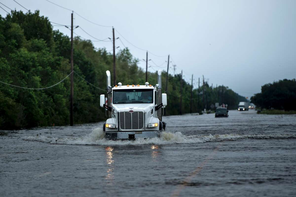 Trucks make their way through flood waters on a main road leading to the Arkema Inc. chemical plant that was in crisis during the aftermath of Hurricane Harvey on August 30, 2017 in Crosby, Texas.