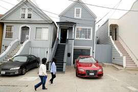Neighbors walk past peak roof Victorian during a broker tour at 415 Amazon Avenue in San Francisco, Calif. on Tuesday, August 29, 2017.