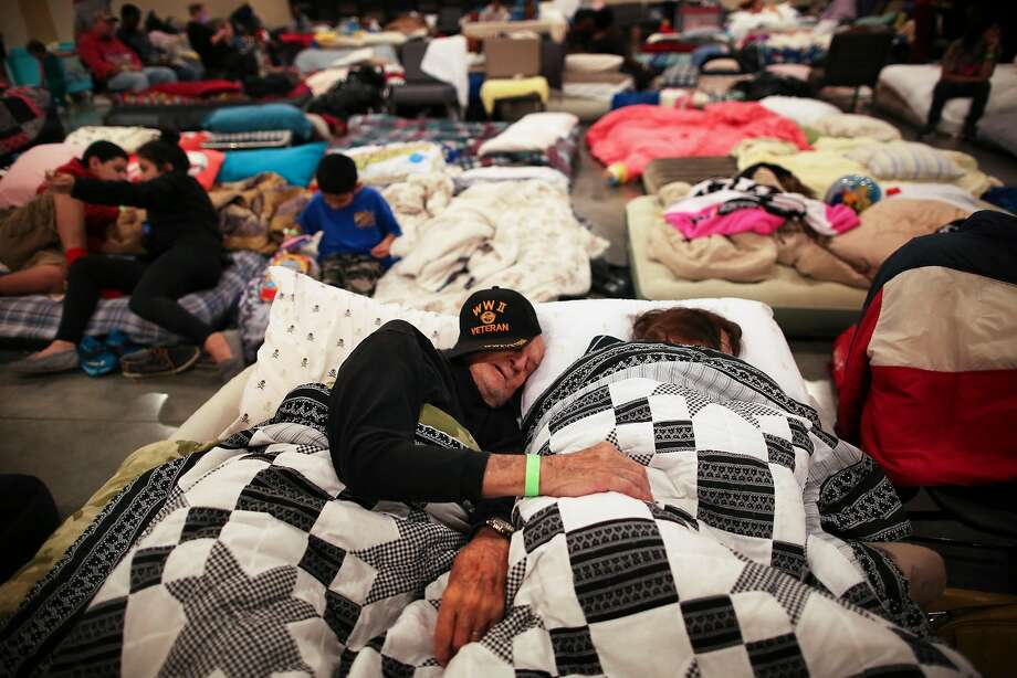 Bob Martin and his wife, Anecita, sleep at a evacuation center set up in Woodlands Church in Woodlands, a suburb of Houston, on Tuesday. Photo: BARBARA DAVIDSON, NYT