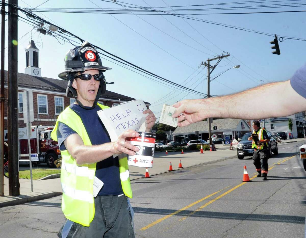 Firefighter Wheatleigh Dunham receives a donation from a person in a vehicle during the Sound Beach Volunteer Fire Company fundraiser to help victims of Hurricane Harvey in front of the firehouse in Old Greenwich, Conn., Wednesday, Aug. 30, 2017. The money collected by the firefighters and volunteers during the fund-raising drive will be given to the Red Cross to help victims of the hurricane that devastated Houston, Texas.