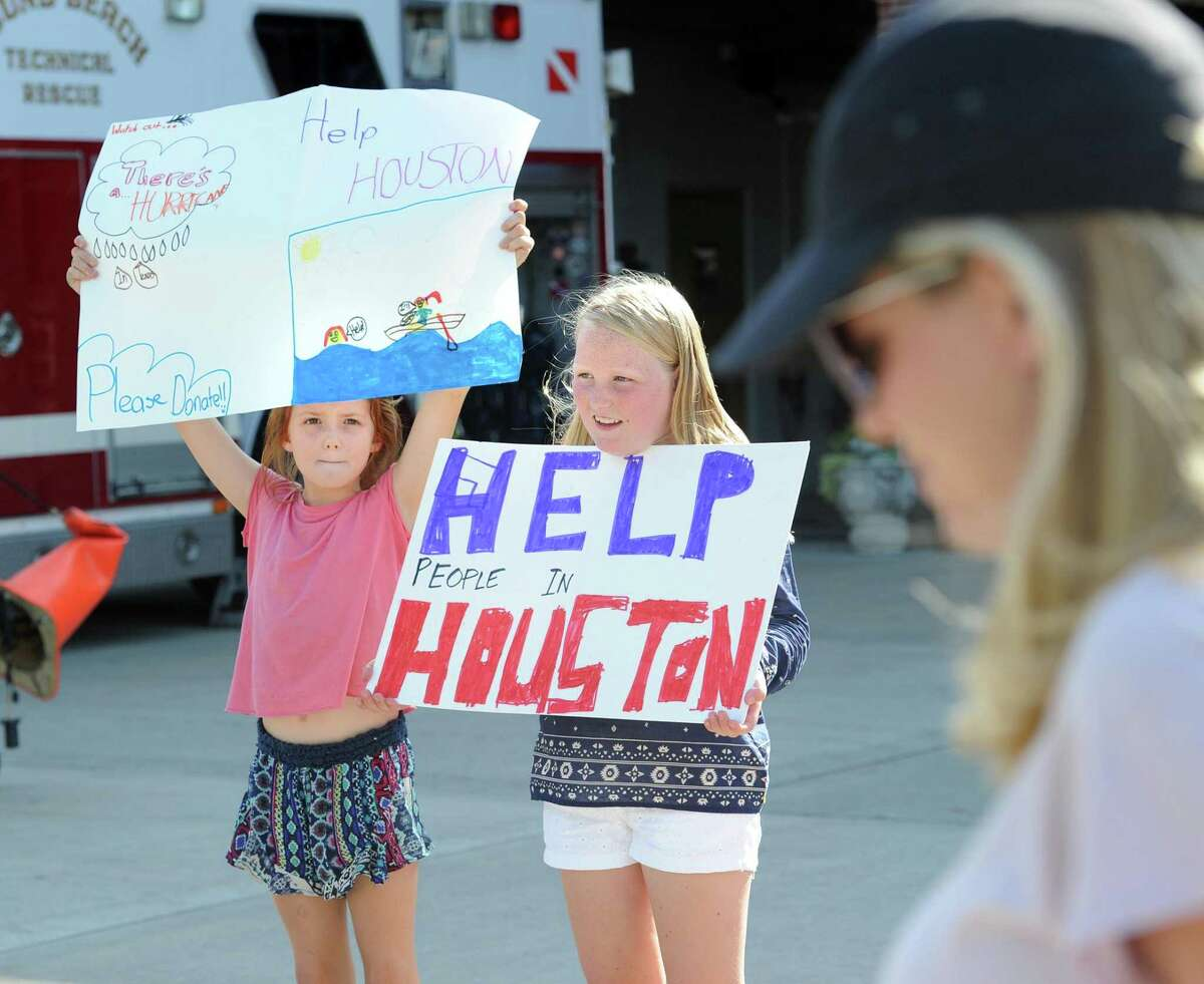 """Julia Trotman, 9, left, and friend Katie McCooe, 11, both of Greenwich, held up """"Help Houston"""" signs during the Sound Beach Volunteer Fire Company fundraiser to help victims of Hurricane Harvey in front of the firehouse in Old Greenwich, Conn., Wednesday, Aug. 30, 2017. The money collected by the firefighters and volunteers during the fund-raising drive will be given to the Red Cross to help victims of the hurricane that devastated Houston, Texas."""