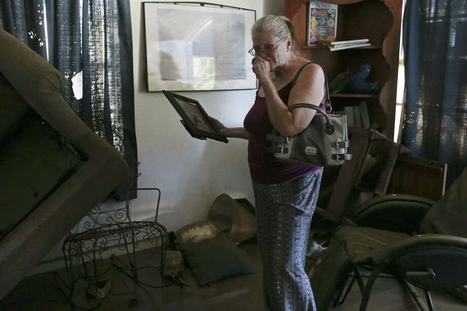 Brenda Smith, 60, gets emotional after returning to her house in La Grange, Texas, Wednesday, August 30, 2017. Smith's house and many others in an area were flooded by the Colorado River with rains from Hurricane Harvey. Photo: JERRY LARA / San Antonio Express-News / San Antonio Express-News