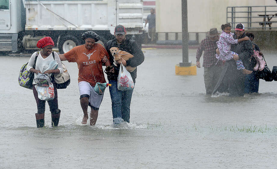 Evacuees make their way through the flood waters that surrounded part of the Max Bowl, which was converted to a shelter for those displaced by flooding in Port Arthur.  Photo taken Wednesday, August 30, 2017 Kim Brent/The Enterprise Photo: Kim Brent / BEN