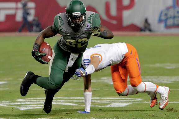 Baylor running back Terence Williams (22) escapes the grasp of Boise State safety Kekoa Nawahine (10) during the first half of the Cactus Bowl NCAA college football game, Tuesday, Dec. 27, 2016, in Phoenix. (AP Photo/Rick Scuteri)