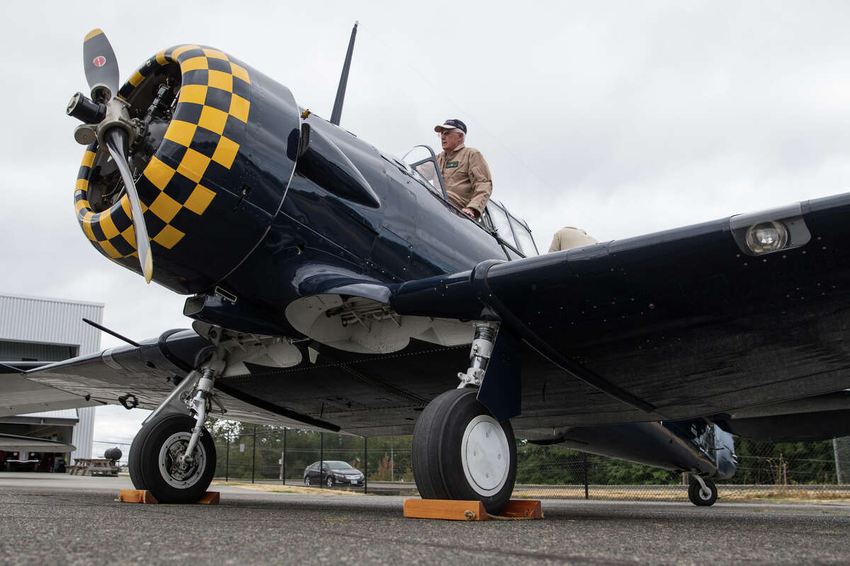Volunteer pilot Bob Jones climbs into Historic Flight Foundation's North American AT-6 Texan for a media preview of Vintage Aircraft Weekend at Paine Field on Wednesday, Aug. 30, 2017.