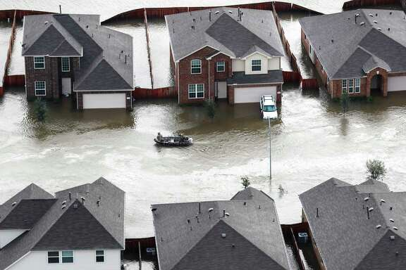 A boat runs past houses flooded by Tropical Storm Harvey on Tuesday in Spring. ( Brett Coomer / Houston Chronicle )