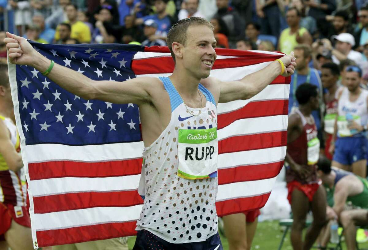 U.S. Galen Rupp celebrates holding a flag after he won the bronze medal in the men's marathon at the 2016 Summer Olympics in Rio de Janeiro, Brazil, Sunday, Aug. 21, 2016.