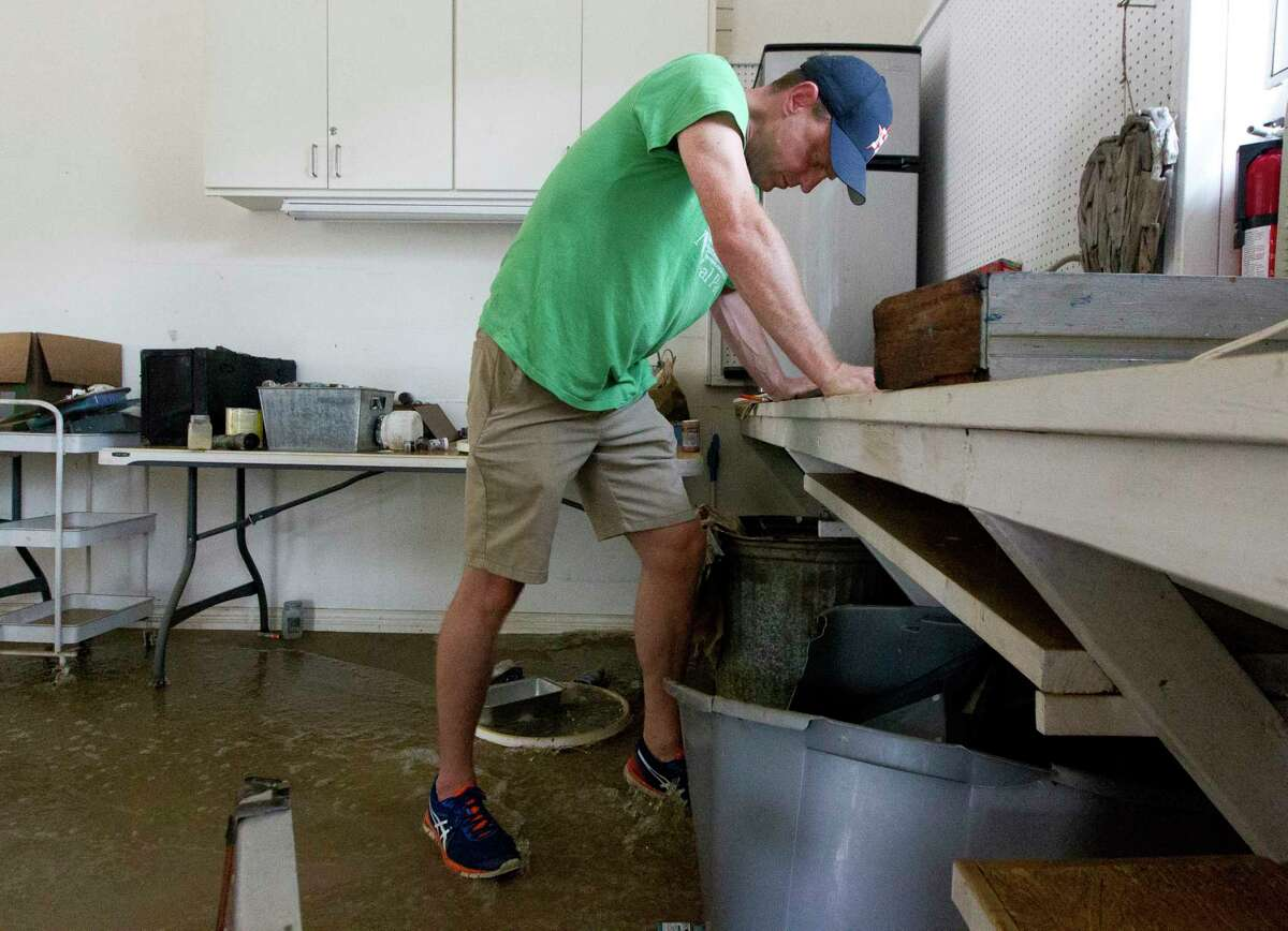 Mike Bartlow kicks a container to drain the water after Tropical Storm Harvey dumped 20 inches inside his River Planation home, Wednesday, Aug. 30, 2017, in Conroe.
