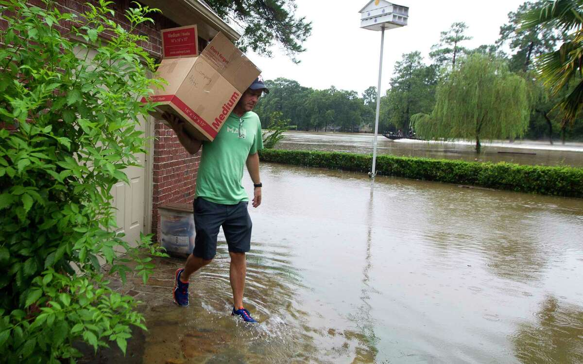 Mike Bartlow carries items out of his house through flood water as his family evacuates their home in River Plantation, Monday, Aug. 28, 2017, in Conroe.