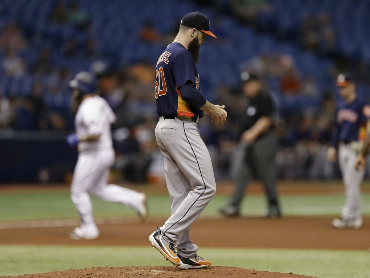 Houston Astros starting pitcher Dallas Keuchel walks back to the mound as Texas Rangers' Mike Napoli runs around the bases after Napoli hit a three-run home run during the fourth inning of a baseball game Wednesday, Aug. 30, 2017, in St. Petersburg, Fla. The Astros moved their three-game home series against the Rangers to St. Petersburg after being displaced by Hurricane Harvey. (AP Photo/Chris O'Meara)