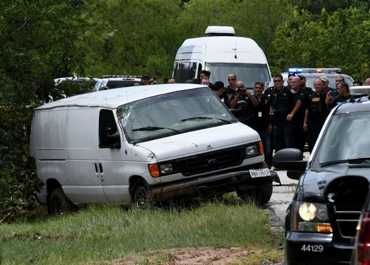 Police investigators watch as the van containing the six members of the Saldivar family who died is towed to the road Wednesday.