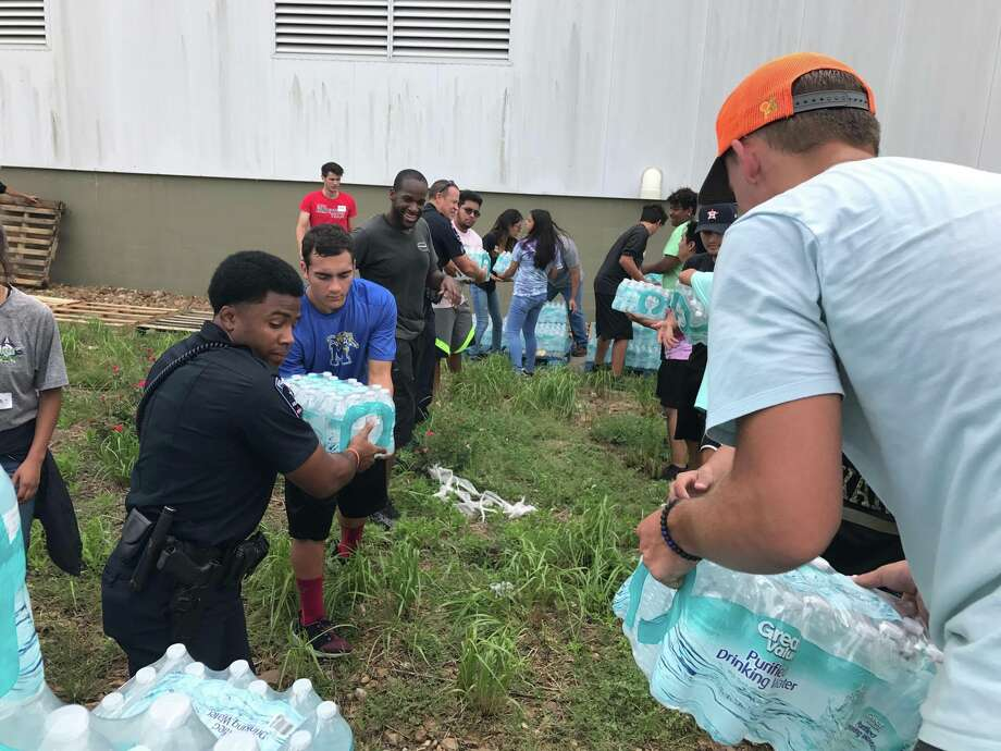 Cox ATA Martial Arts School students from Conroe and Magnolia joined by Arlington Police Officers helped unload the 12,500 bottles of water delivered to  Falcon Steel America donation site Wednesday from Austin by Mike Niblock and his son-in-law, U.S. Army Veteran Darren Wing.