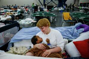 Shiann Barker holds her nephew, Brayln Matthews Sims Jr., 1, between cots at the George R. Brown Convention Center where nearly 10,000 people are taking shelter after Tropical Storm Harvey Wednesday, Aug. 30, 2017 in Houston. They have ben at the shelter since Sunday after they evacuated from the Clayton Homes neighborhood. ( Michael Ciaglo / Houston Chronicle)