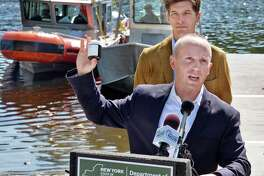 DEC Commissioner Basil Seggos holds up one of 1600 samples collected from the upper Hudson River during a news conference calling for continued PCB clean-up in the river Wednesday August 30, 2017 in Moreau, NY. Scenic Hudson's Andy Bicking at top.  (John Carl D'Annibale / Times Union)