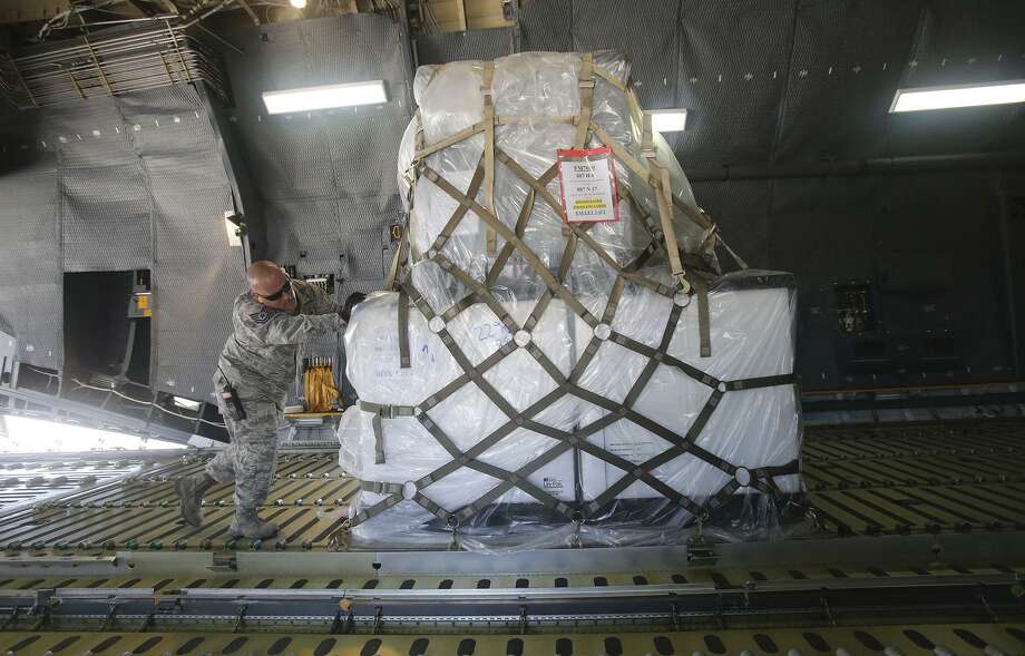 Loadmasters push relief supplies into place on a C-5 Galaxy aircraft Wednesday August 30, 2017 that will be delivered to victims of hurricane/tropical storm Harvey by the 433rd Airlift Wing from San Antonio, Texas to Houston, Texas. Medical supplies and water make up a large portion of the 80,000 pounds of supplies being delivered to the area. Photo: John Davenport, STAFF / San Antonio Express-News / ©John Davenport/San Antonio Express-News
