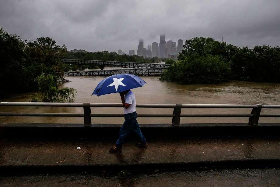 Armando Bustamante walks along Studemont Street over flooded Buffalo Bayou during Harvey. Photo: Michael Ciaglo, Staff / Michael Ciaglo