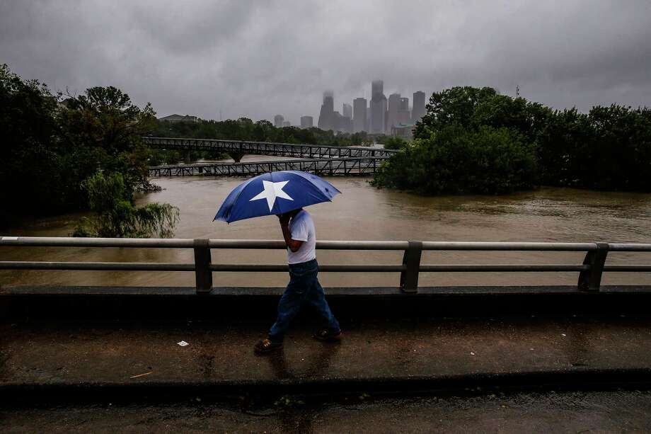 Armando Bustamante walks along Studemont Street over flooded Buffalo Bayou during Harvey. Photo: Michael Ciaglo, Staff / Michael Ciaglo