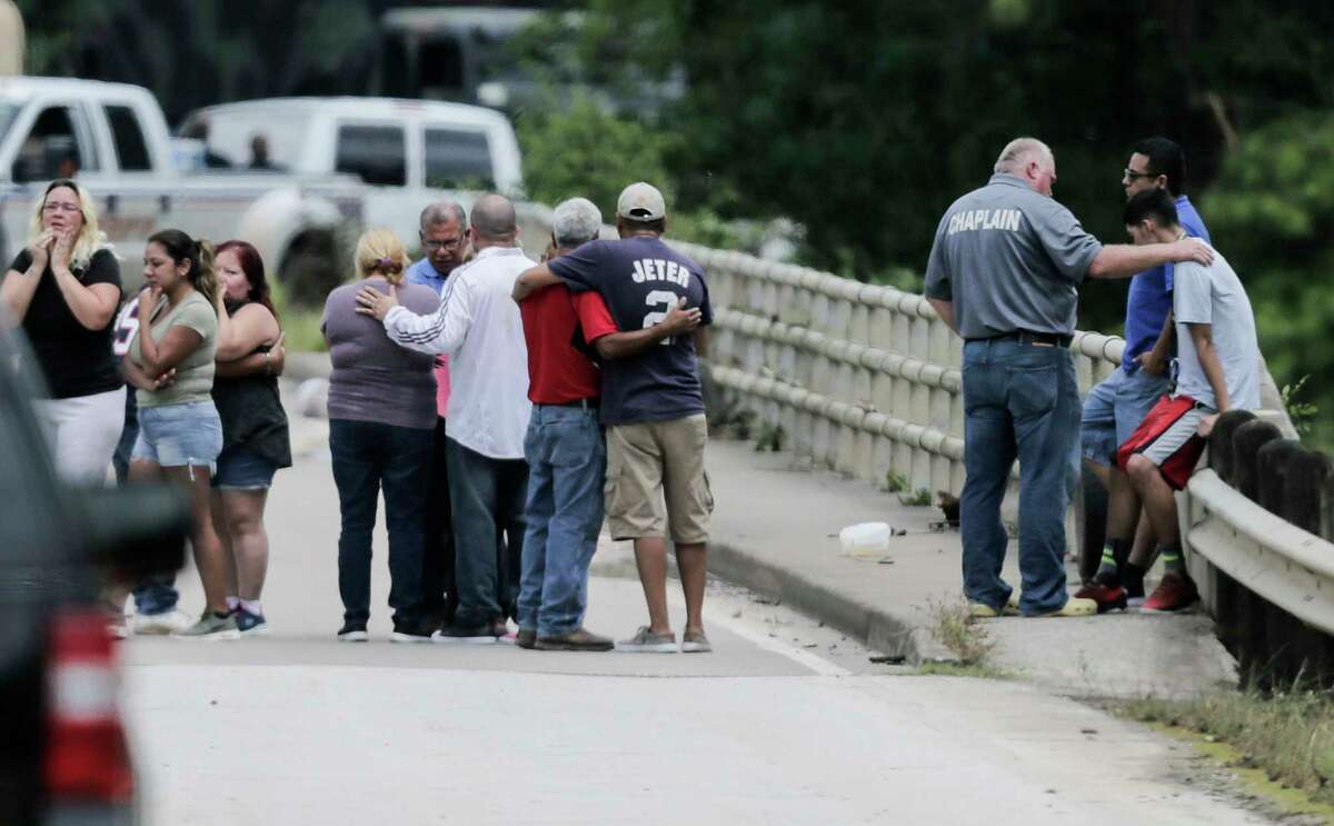 Relatives console one another as a van is pulled out of Greens Bayou with the bodies of six family members Wednesday.