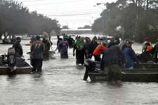 Rescue workers carry patients from nearby flooded nursing homes down by boat down Jimmy Johnson Boulevard on Wednesday in Port Arthur. (Mike Tobias/The Enterprise)