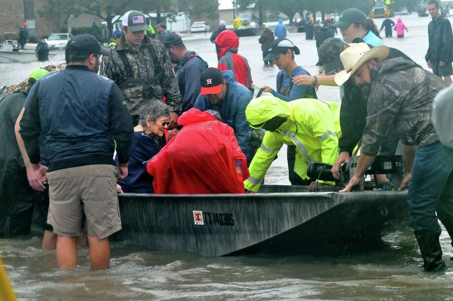 Rescue workers carry patients from nearby flooded nursing homes down by boat down Jimmy Johnson Boulevard on Wednesday in Port Arthur. (Mike Tobias/The Enterprise) Photo: Mike Tobias/The Enterprise