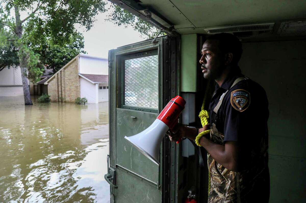 Harris County Sheriff's Deputy Rick Johnson pauses to listen for people's voices as they search for people in a neighborhood inundated by water from the Addicks Reservoir, Wednesday, Aug. 30, 2017, in Houston. (Jon Shapley/Houston Chronicle via AP)