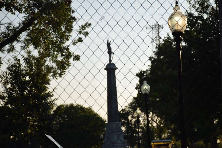 Officials on Thursday erected a fence around Travis Park as city council members prepared to vote on whether to remove the Confederate memorial from the park. Photo: Caleb Downs / San Antonio Express-News