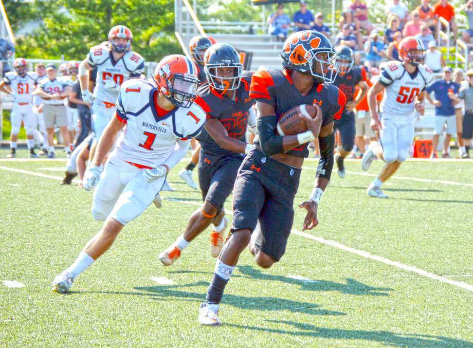 Edwardsville wide receiver Donovan Booker, right, looks for running room in the second quarter of a game against Naperville North at the District 7 Sports Complex.