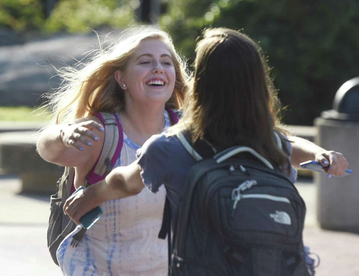 Sophomores Ellie Marullo, left, and Sydney Nethercott hug after being reunited on the first day of the 2017-2018 school year at Greenwich High School in Greenwich, Conn. Thursday, Aug. 31, 2017. The high school's start time this year is 8:30 a.m., one hour later than previous years. In addition, the three middle schools begin at 8 a.m., 15 minutes later than in the past, while all 11 elementary schools begin at the same time.