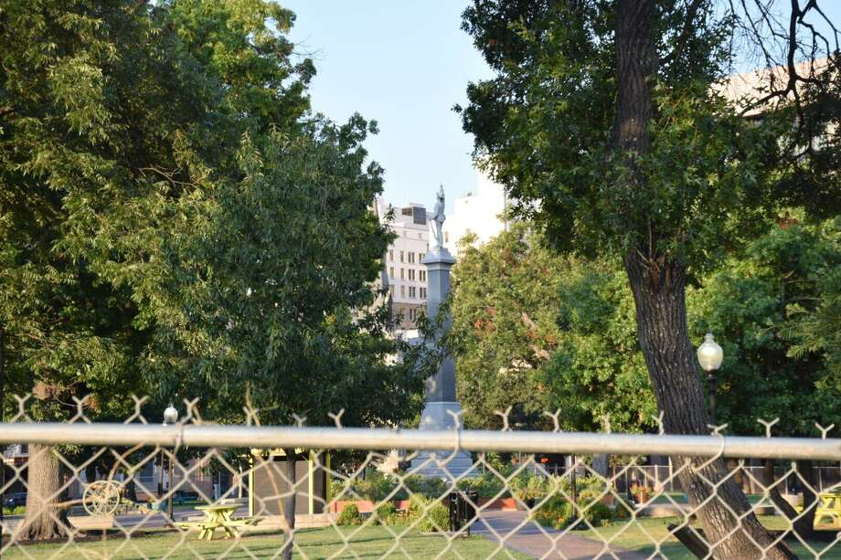 Officials on Thursday erected a fence around Travis Park as city council members prepared to vote on whether to remove the Confederate memorial from the park. Photo: Caleb Downs / Caleb Downs / San Antonio Express-News