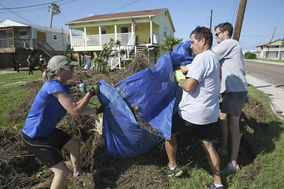 James Racanelli (center) gets his daughter Christina and friend Baxter Perkins to dump some of the debris washed up on their house out near the street where it can be picked up and hauled away as recovery proceeds in Port Aransas  on August 30, 2017. Photo: Tom Reel, Staff / San Antonio Express-News / 2017 SAN ANTONIO EXPRESS-NEWS