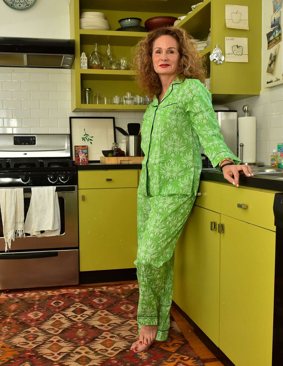 Sonya Dawson is shown in her King William-area kitchen in green pot-patterned pajamas.
