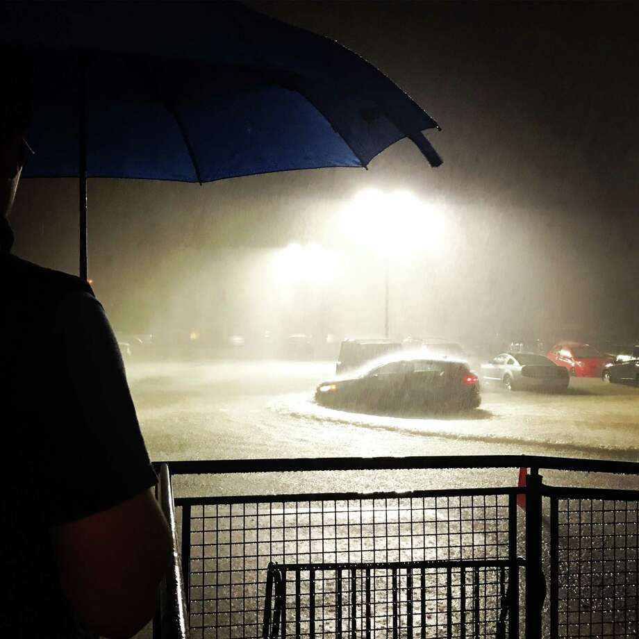 Harvey's rains classify it as what was thought to be a 1,000-year storm. In this photo: An apartment resident watches water accumulate in his parking lot on Saturday, Aug. 26, 2017. Photo: Elizabeth Conley, Harvey2017 / Houston Chronicle